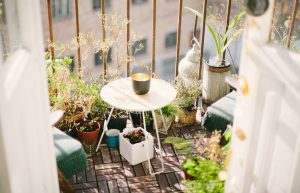 Apartment balcony with tiny table and chairs surrounded by a jungle of plants