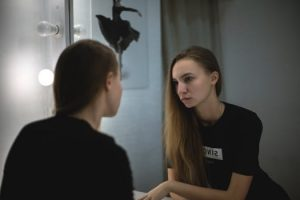 Woman with sad expression looks in the mirror before her cosmetic surgery Glasgow consultation