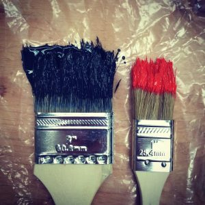 Paintbrushes laid on plastic on the floor being used to decorate