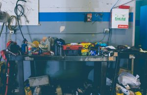 Workbench for garage and workshop covered in equipment in a dark and dirty room