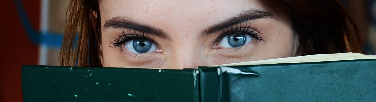 Close up of woman's eyes peering over a book to suggest you can guess the stage of ageing through the eyes